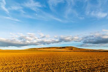 Campos de cultivo de secano, lomas y cielo azul con nubes. Comarca de Los Oteros.