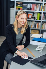 Happy young businesswoman working at her computer
