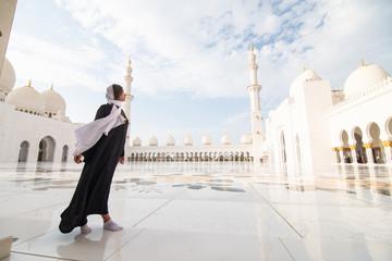 Poster Abou Dabi Traditionally dressed arabic woman wearing black burka visiting Sheikh Zayed Grand Mosque in Abu Dhabi, United Arab Emirates.