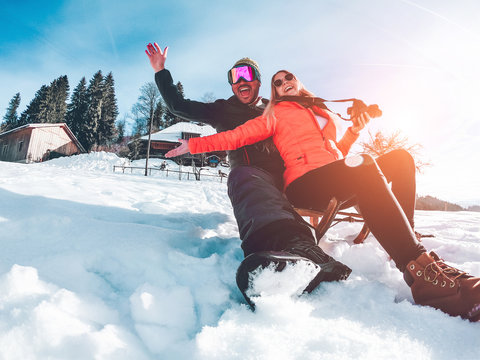 Happy influencers couple having fun with wood vintage sledding on snow high mountains - Young crazy people enoying winter vacation - Travel and holiday concept