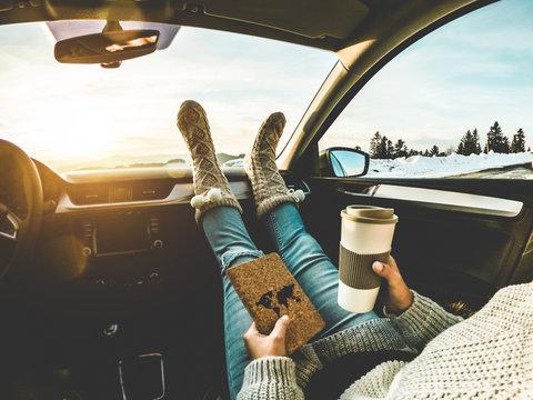 Woman drinking coffee paper cup inside car with feet warm socks on dashboard