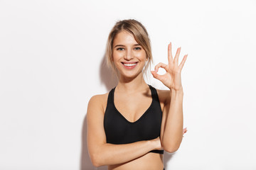 Fitness woman isolated over white wall background showing okay gesture.