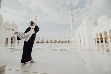Poster Abou Dabi Traveling by Unated Arabic Emirates. Young woman in traditional abaya standing in the Sheikh Zayed Grand Mosque, famous Abu Dhabi sightseeing.