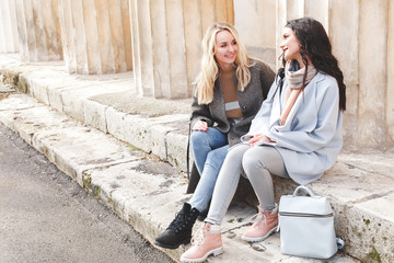Two young beautiful girls, blonde and brunette, in gray and blue coat sitting on the steps, talking and smiling. Two girl friends relaxing outdoors in the city. Fashion, street casual outfit.