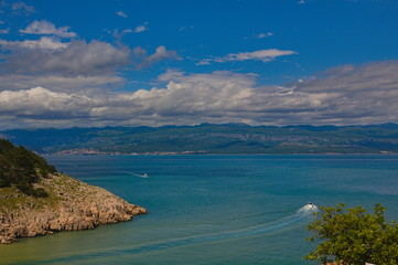 Scenic view from the island Krk towards the croatian mainland with clouds and a blue sky