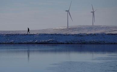 A man walks across snow covered moorland near Todmorden.