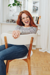 Laughing young woman seated on a chair