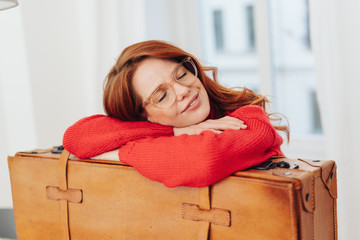Young woman leaning on a vintage suitcase