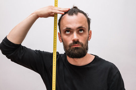 a man with a beard and a black t-shirt makes measurements of his height with a tape measure