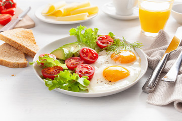 healthy breakfast with fried eggs, avocado, tomato, toasts and coffee