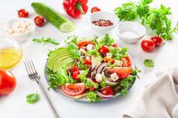 greek style avocado tomato salad with feta cheese, olives, cucumber, onion, lettuce