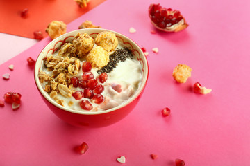 Tasty granola with yogurt and pomegranate seeds in bowl on color background