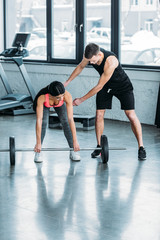 male trainer helping sporty african american girl lifting barbell in gym