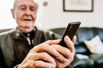Senior surft zuhause mit seinem smart phone im Internet