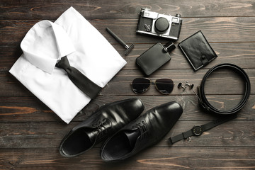 Stylish male clothes with accessories and photo camera on wooden table