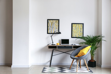 Stylish workplace with modern computer near white wall
