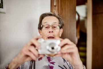 Seniorin fotografiert mit einer Kamera