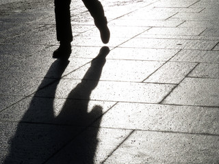 Black silhouette and shadow of man walking down the street. Hurrying man outdoors, pedestrian, concept for dramatic life stories
