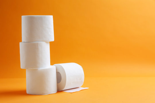 Rolls of toilet paper on color background