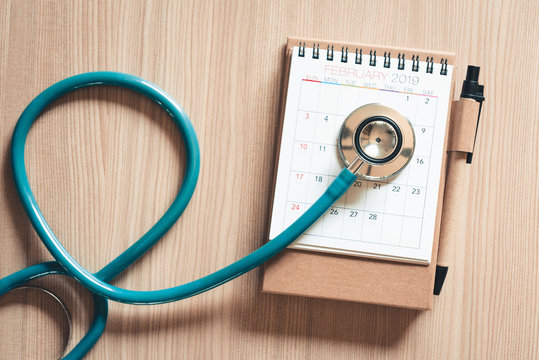 Top view of stethoscope on calendar for health checkup concept., Annual doctor appointment for physical check-up against wooden background., Healthcare Medicine and Insurance concept.