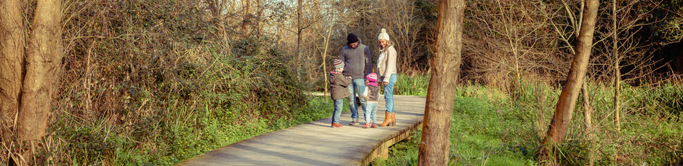 Happy family speaking and playing together over a wooden pathway into the forest