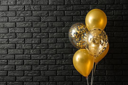 Bright balloons near dark brick wall