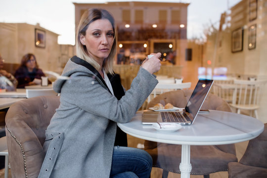 Portrait of businesswoman having coffee while working on laptop in cafe