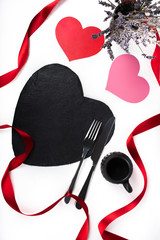Heart shaped black plate dinner or lunch table setting for valentine day romantic celebration