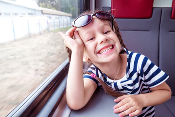 little girl on the train looks out the window
