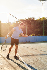 Sunlit tennis player ready to serve