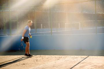 Sunlit tennis athlete on court