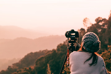 Young woman photographer taking picture of landscape when sunrise  at mountain peak.Travel and hobbies concept