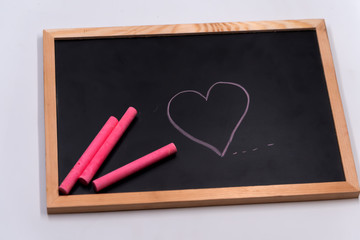 Color chalk put and draw cartoon heart shape on blackbroad.Tell love in valentine day or tell save good health and heart.