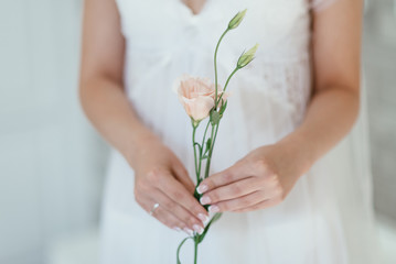 the bride is holding a beautiful flower. soft focus