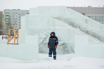 Assembler in overalls on the territory of the ice town