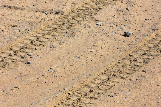 Traces of tire treads on a dry soil surface.