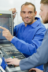 technician pointing to screen of computerised control panel