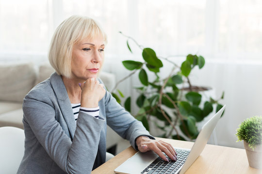 Elderly woman writer in white working on new article