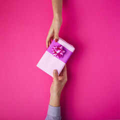 man gives a girl a gift from hand to hand,box wrapped in decorative paper with a bow background, the concept of holidays, love and relationships, top view