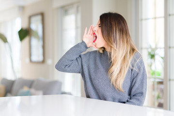 Young beautiful woman wearing winter sweater at home shouting and screaming loud to side with hand on mouth. Communication concept.