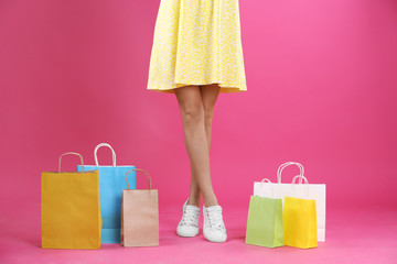 Young woman with shopping bags on color background, closeup