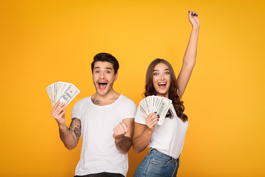 Happy couple holding bunch of money banknotes