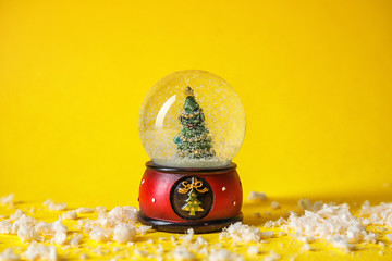 Snow globe with Christmas tree on color background