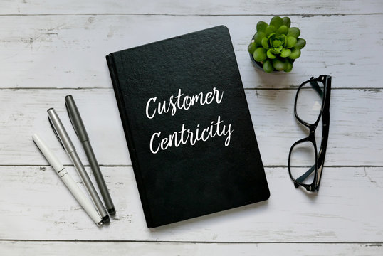Business concept. Top view of glasses,plant,pen and notebook written with Customer Centricity.