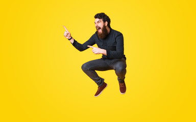 Portrait of bearded man screaming and jumping over yellow background and pointing away Wall mural