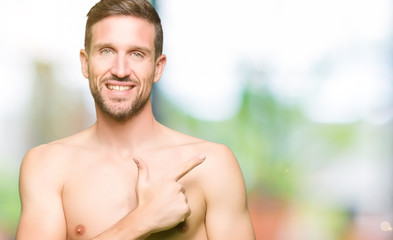 Handsome shirtless man showing nude chest cheerful with a smile of face pointing with hand and finger up to the side with happy and natural expression on face