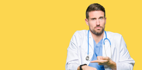 Handsome doctor man wearing medical uniform over isolated background In hurry pointing to watch time, impatience, upset and angry for deadline delay