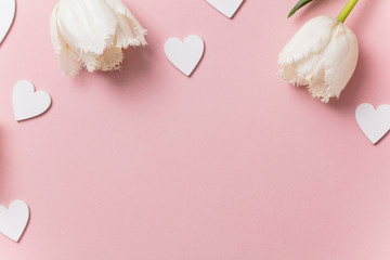White flowers and hearts on a pastel pink background
