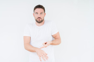 Young handsome man wearing casual white t-shirt over isolated background In hurry pointing to watch time, impatience, upset and angry for deadline delay