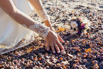 Hands of a bride playing with snail shells on the beach